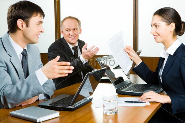 Трое коллег общаются сидя за столом