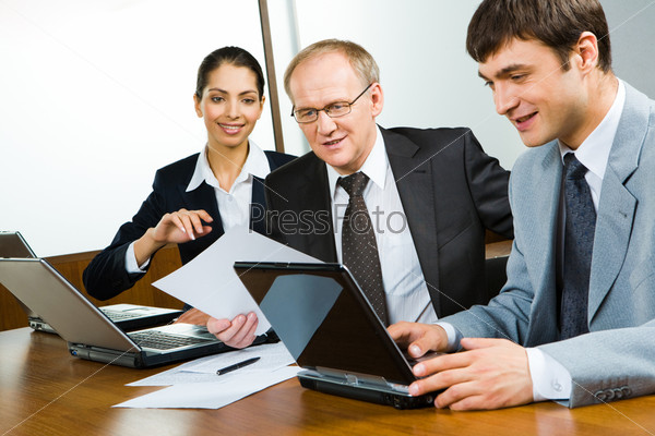 Деловые люди работают с документами и ноутбуком в офисе