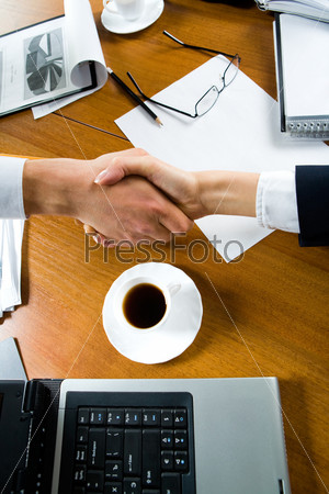 up of people making a deal with a handshake over the table