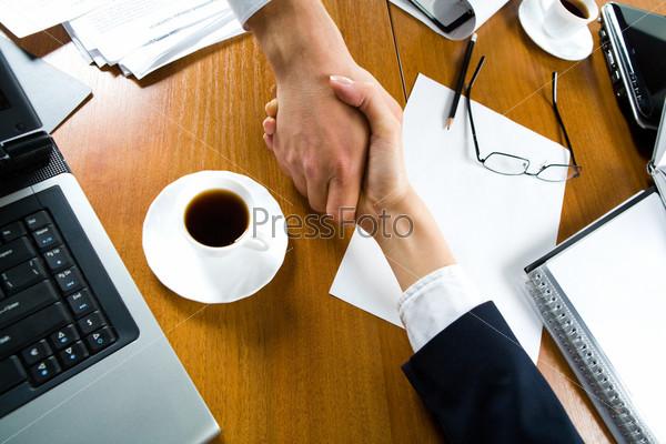 Рукопожатие деловых людей над рабочим местом