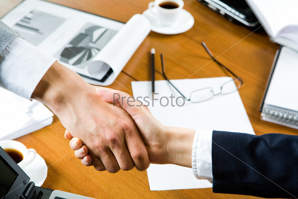 Business people's handshake over table with business objects on it