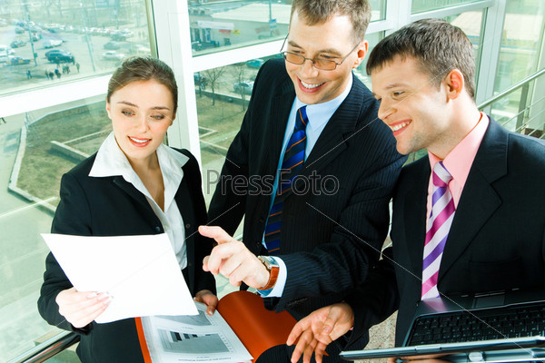 Photo of business people looking at the document at meeting