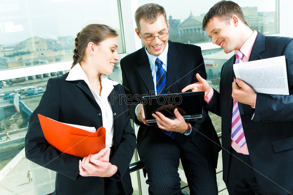 Business partners looking at the laptop on the background of window