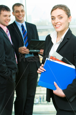 Portrait of business woman holding the folders on the background of businessmen
