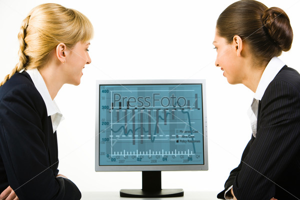 Portrait of two business ladies looking into the computer screen