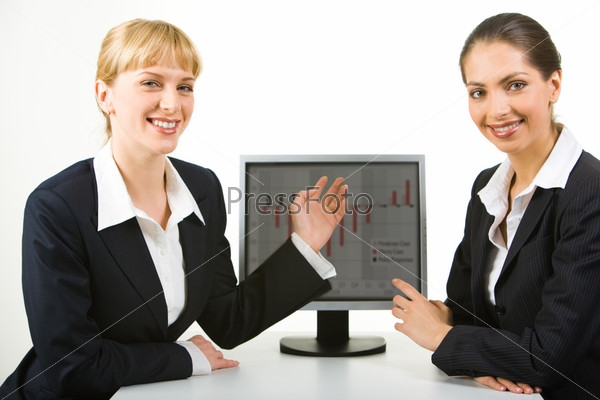 Portrait of two businesswomen sitting near computer and pointing at its monitor