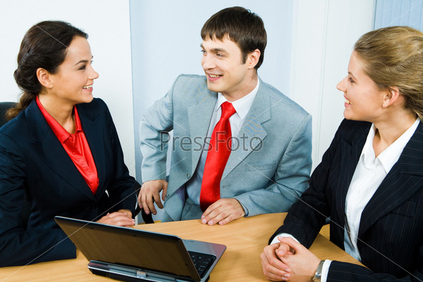 Image of businesspeople chatting and sitting at the table