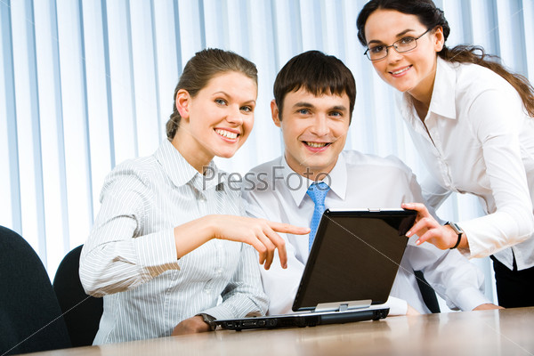 Team of three businesspeople gathered around the table with laptop and working