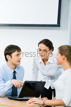 Image of three employees discussing a computer work