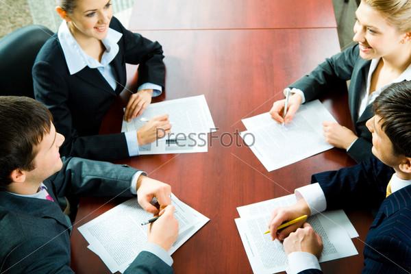 Деловые партнеры сидят за столом с документами, смотря на них