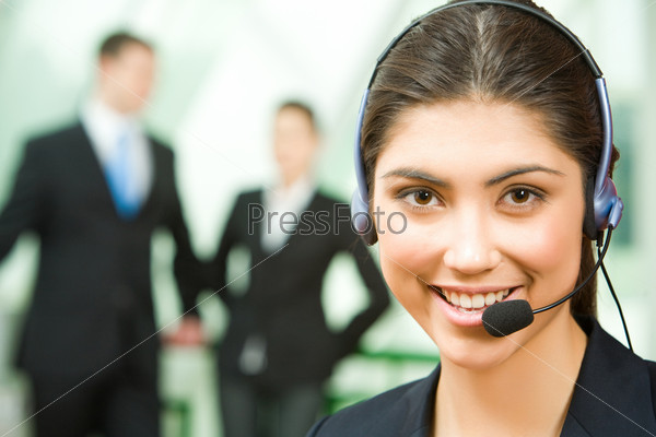 Portrait of friendly consultant with headset on the background of people