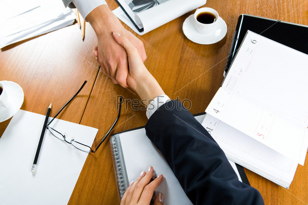 Image of handshake of partners over table with business objects on it