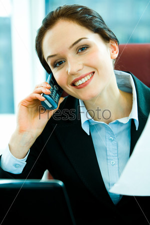 Confident young woman calling by cellphone in the office