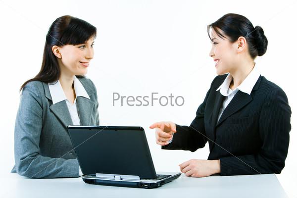 Две деловые женщины сидят за ноутбуком, и одна из них указывает на экран