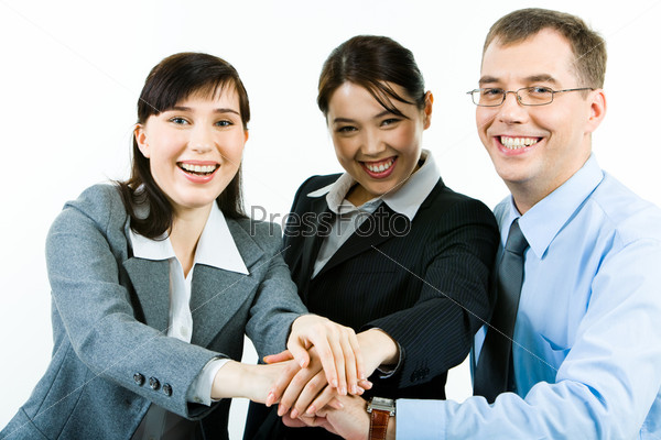 Portrait of three business partners making pile of their hands and looking at camera