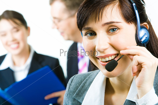 Closeup of young woman with headset looking at camera with smile