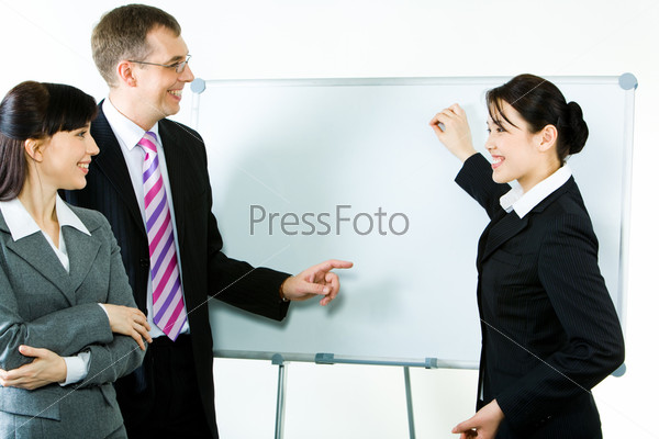 Photo of young businesswoman showing something on whiteboard with smile