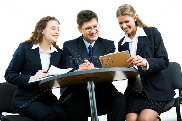 Group of three business people sitting at the table and working