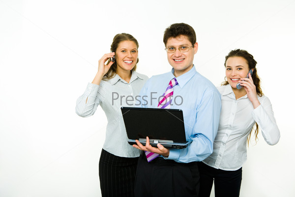 Portrait of confident man with two business women near by calling by phones