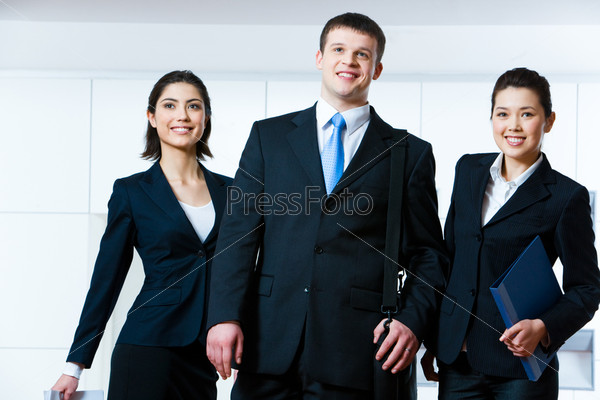 Portrait of business people standing next to each other and looking forwards