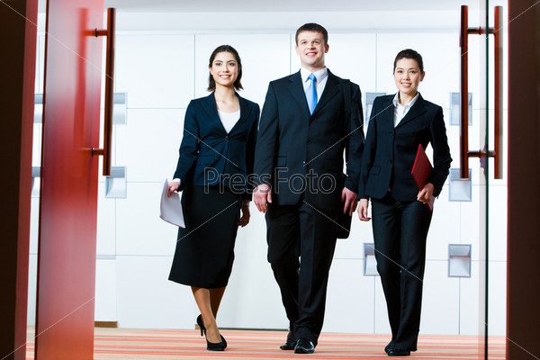 business partners standing in front of open doors and going to enter conference hall