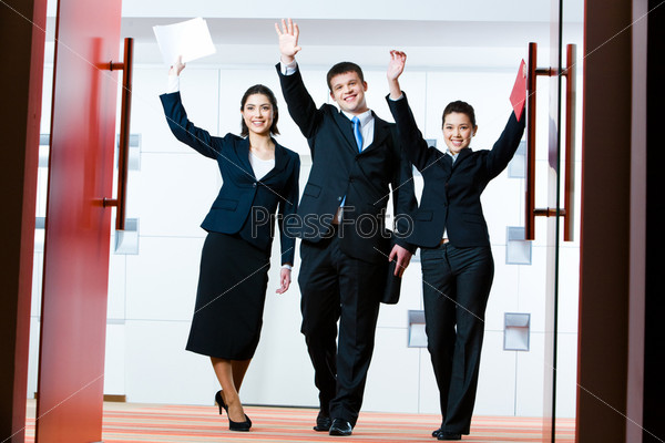 Portrait of successful business group  at the door of conference hall with raised hands