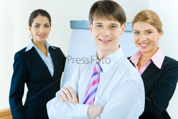 Portrait of successful businessman with smile with two pretty ladies behind