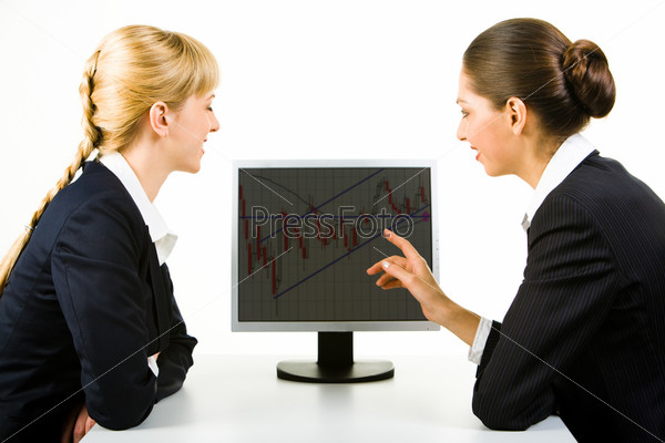 Photo of two businesswomen sitting in front of computer and looking at its screen