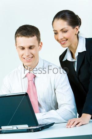 Двое молодых деловых людей смотрят на ноутбук