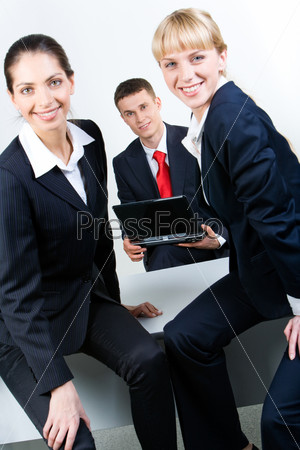 Image of smiling business women sitting on the table in front