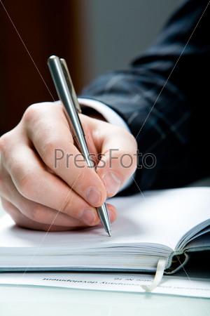 Мужская рука крупным планом с ручкой над блокнотом