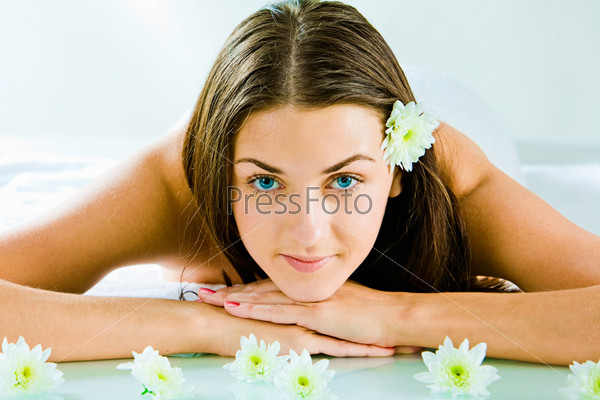 Portrait of attractive girl looking at camera and lying in the salon