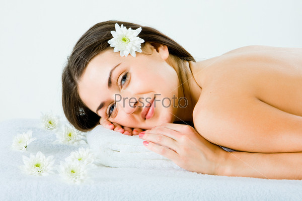 Image of charming woman lying on the towel with flowers