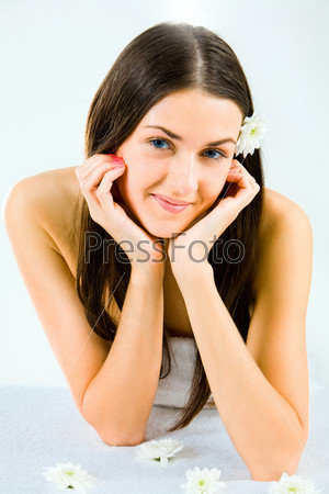 Portrait of nice smiling brunette with white chrysanthemum in her hair