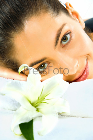 up of beautiful young woman with a white fine flower near by