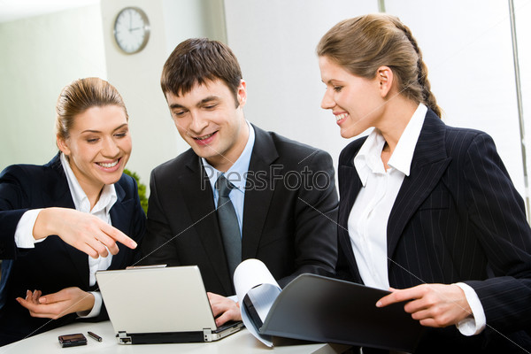Деловая команда сидит за столом и обсуждает работу на компьютере