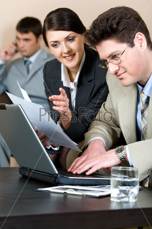 Vertical photo of sitting businessman typing and looking at laptop monitor