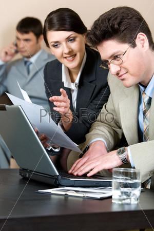 Бизнесмен сидит и набирает текст на ноутбуке, смотря на экран