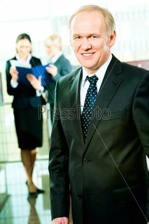 Опытный менеджер стоит в офисе на фоне деловых женщин