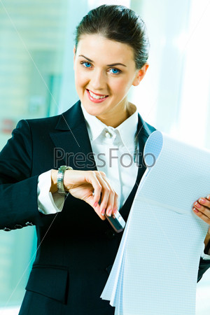 Portrait of busy woman raising her hand with watch and holding the phone, notepad