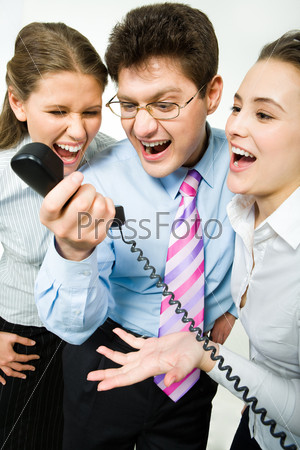 Closeup of three business people screaming into the phone receiver during their work