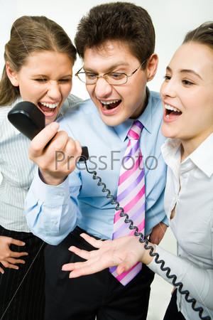 Трое деловых людей кричат в телефонную трубку во время работы