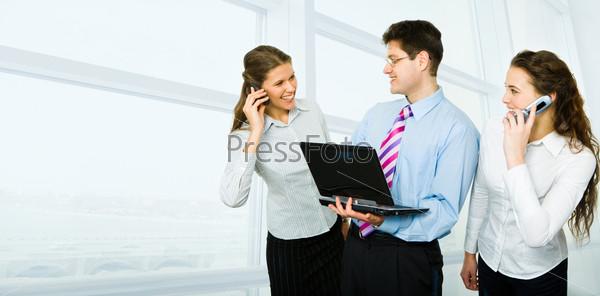 Бизнесмен стоит между двумя женщинами, разговаривающими по телефонам
