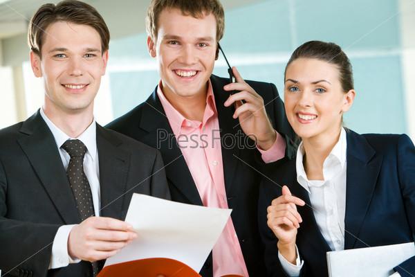 Счастливая деловая группа смотрит в камеру с улыбками
