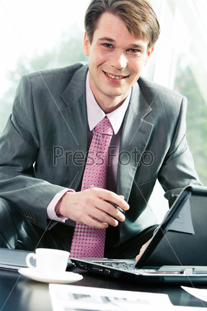Portrait of handsome businessman sitting at the table in the room