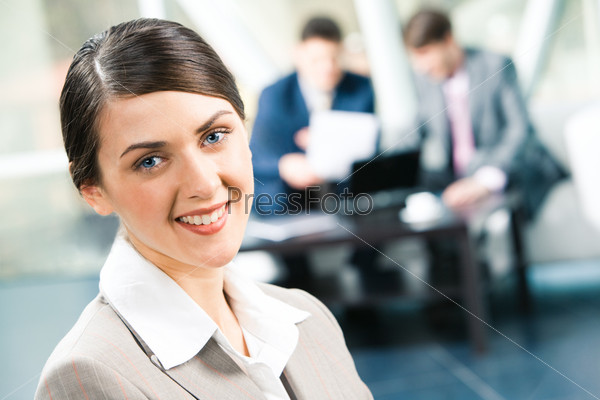 Image of beautiful business woman looking at camera in a working environment