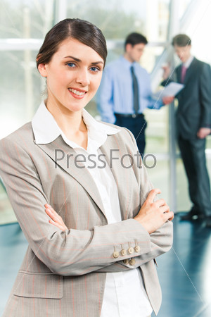 Portrait of smart specialist folding the hands on the background of business people