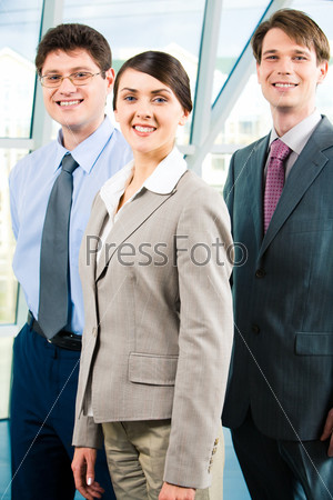 Team of three business people with leader in front