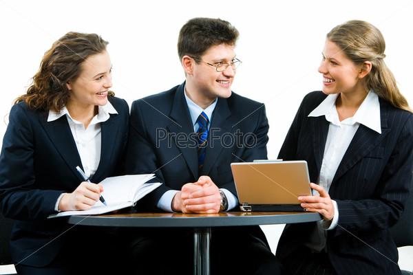 Деловые люди сидят за столом и беседуют