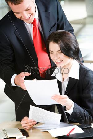 Бизнесмен указывает на документ в руках женщины